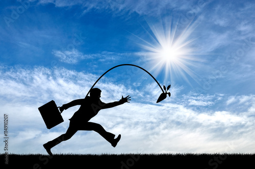 Fototapeta Silhouette of businessman running for the carrot.