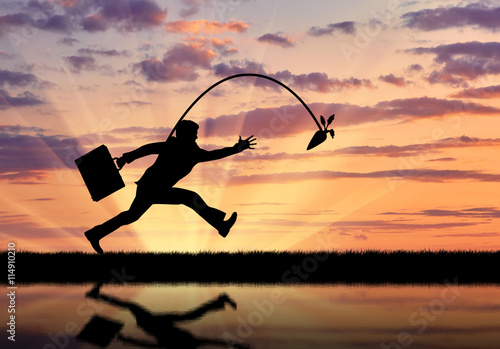 Fototapeta Silhouette of businessman running for the carrot and reflection in water.