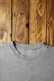 Blank grey t-shirt isolated on wooden rustic table top view on neck part mockup