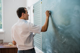 Fototapety Young male teacher or student holding chalk writing on chalkboard in classroom