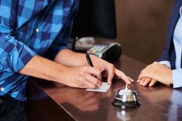 Gast an der Rezeption füllt ein Formular aus