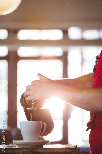 Mid section of waiter pouring a cup of coffee Poster