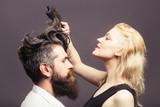 Blond fryzjerka czesze brodatego mężczyznę