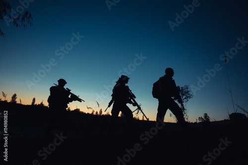 Poster Silhouette of military soldiers with weapons at night. shot,