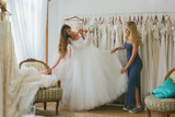 A young bride with her friend choosing wedding dress