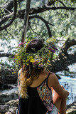 beautiful girl in a wreath of flowers on the banks  the river,   Sunny day.
