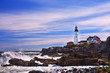 Lighthouse on the ocean, Portland. Maine United States stone cliffs on the raging waves. Sunny clear day. beautiful sky with gentle clouds