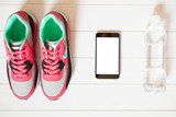 Red sneakers with bottle with water, smartphone with copy space on screen on white wooden background indoors. Smartphone mockup. Sports and fitness background, healthy lifestyle concept.