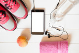 Red sneakers with towel, peach, bottle with water, smartphone with copy space on screen with headphones on white wooden background indoors. Mobile phone mockup.