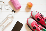 Red sneakers with towel, peach, bottle with water, smartphone with headphones on white wooden background indoors. Sports and fitness background, healthy lifestyle concept.