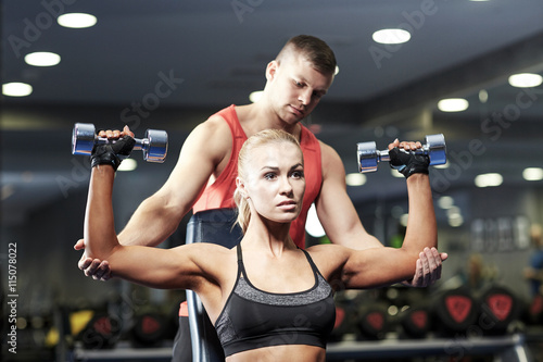 Fototapeta man and woman with dumbbells in gym