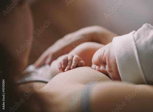 Poster Mother holding her newborn child. Mom nursing baby