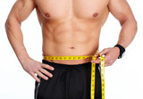 Man abdomen with measuring tape over blue background.