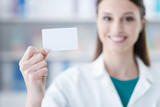 Female doctor holding a business card