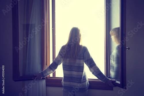 Lonely blonde woman looking through the open window.  - 115104010