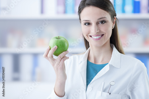Poster, Tablou Dentist holding a green apple