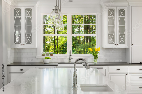 White Kitchen Detail in New Luxury Home: Kitchen Island Quartz with Sink and Cab Poster