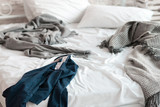 Wrinkled shirt lying on unmade bed closeup. Blue shirt lie about messy bed on wrinkled sheet near gray blankets in the morning.