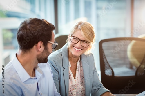 Poster Businesswoman interacting with a colleague
