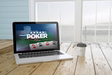 laptop with poker online website on screen with port background