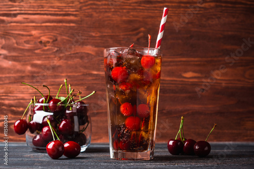 Poster Refreshing cold cherry cola on the wooden background