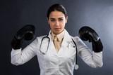 Ragazza con camice da medico, dettaglio guantoni da pugilato e stetoscopio.