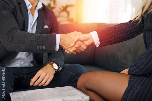 Businessman handshake with businesswoman in sunset плакат