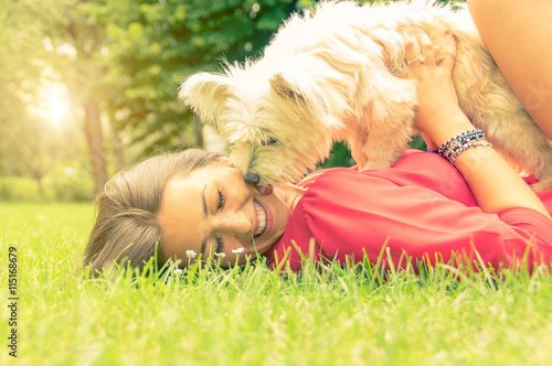 Plakat White dog kissing it's owner lying on the grass