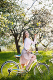 Pretty female with a retro bicycle in the lush green grass enjoying flowers of a blossoming tree in the ray of sunshine in a spring garden