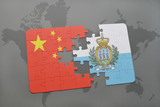 puzzle with the national flag of china and san marino on a world map background.