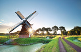 Fototapety morning sunshine behind Dutch windmill