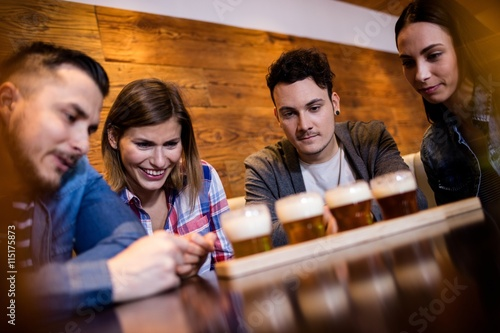 Friends looking at beer glasses in restaurant Canvas