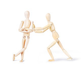 Man pushes another one to move him from his position. Abstract image with wooden puppets