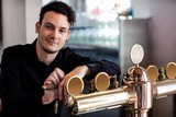 Handsome bartender leaning on beer tap
