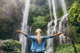 Fototapety Woman standing by waterfall with her hands raised