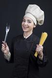 Cuoco donna su sfondo nero con posate e pasta in mano