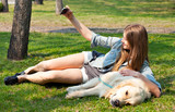 Girl and her dog selfie summer on a background of green grass..