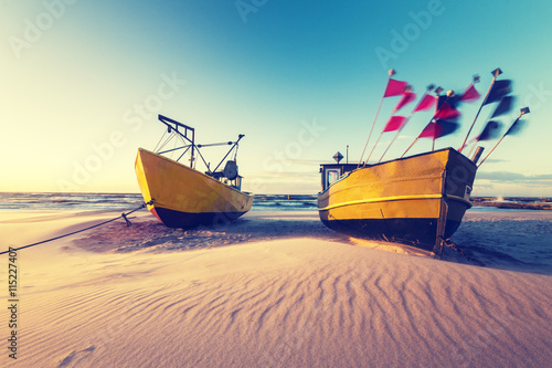 Vintage retro stylized photo of fishing boats on the sea beach