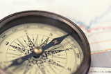 A compass on charts. A direction of success. Warm toned
