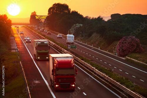 fototapeta na ścianę trucks in the highway at sunset