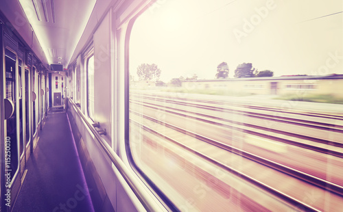 Vintage toned train window with motion blurred rails outside.
