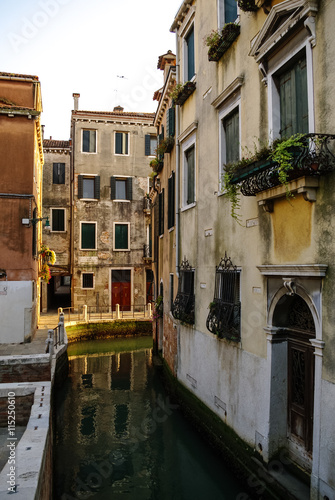Narrow canal among old colorful brick houses in Venice, Italy