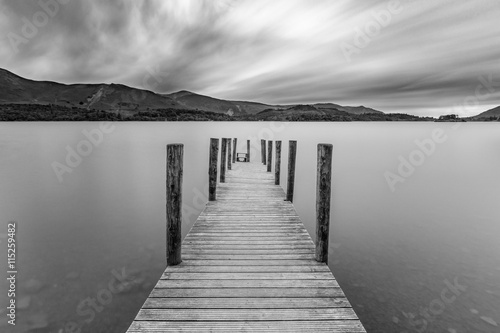 Acrylglas Pier Long wooden jetty at Derwentwater Lake with moody dramatic clouds. Keswick, Lake District, UK.