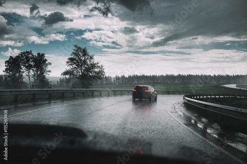 Foto op Canvas Stadion Drive car in rain on curve asphalt wet road