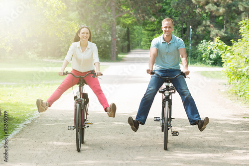 Zdjęcia na płótnie, fototapety, obrazy : Happy Couple Riding Bicycle In Park