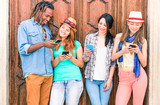 Multiracial group of friends texting sms and looking down to cell phone - Multicultural row of students using mobile - Concept of teens addiction to web social network technology