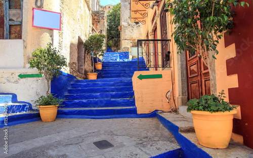 Ultramarine stairs with orange pots with trees. The picture taken in the town Symi, Greece