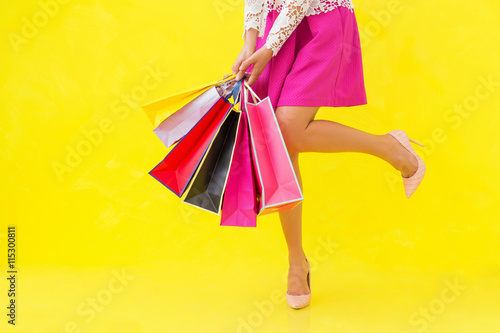 Woman with sexy legs holding shopping bags