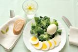 pranzo estivo vegetariano, una fresca insalata con uovo sodo e una fetta di pane integrale