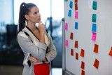 Woman looking at adhesive notes in office